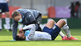 Injured - Aston Villa midfielder Trezeguet receives medical attention during a Premier League match against Liverpool at Anfield on Saturday