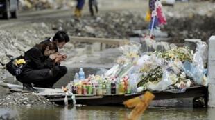 Familiares fazem uma homenagem as vítimas de uma escola primária destruída durante o terremoto do 11 de março em Ishinomaki, no Japão..