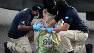 Miembros de la Agencia Técnica de Investigación Criminal de Honduras retiran  paquetes de cocaína decomisados de una bolsa, en la base aérea de Hernán Acosta Mejía en Tegucigalpa, el 11 de enero de 2021