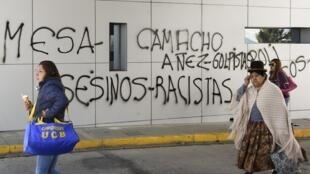 Des femmes marchent à côté d'un graffiti portant l'inscription «Mesa-Camacho-Anez, assassins-racistes» à un poste de péage sur la route reliant El Alto et La Paz bloquées par des partisans de l'ex-président Evo Morales à El Alto, en Bolivie, le 19/11/19.