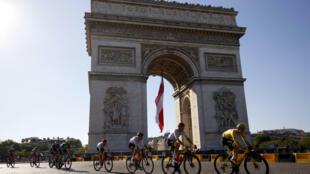 Le Slovène Tadej Pogacar (d) devant l'Arc de Triomphe lors de la 21e et dernière étape du Tour de France, entre Chatou et Paris, le 18 juillet 2021