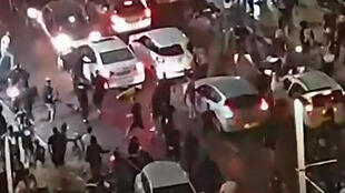 This video grab obtained from footage released by Kan 11 public broadcaster  shows a far-right Israeli mob attacking who they considered an Arab man, on the seafront promenade of Bat Yam, a town south of Tel Aviv