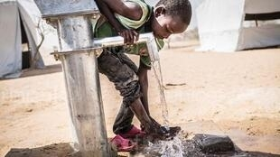 A child drinks from a water fountain installed by Unicef