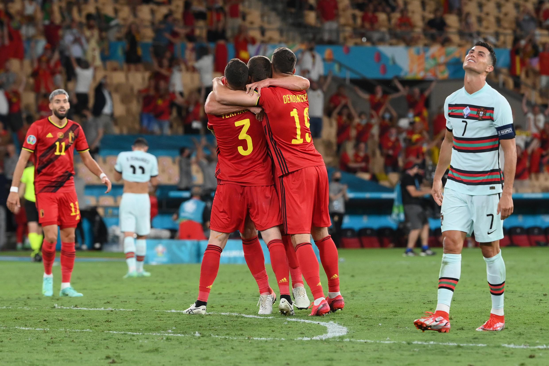 El delantero portugués Cristiano Ronaldo (D) lamenta la eliminación de su selección, mientras los futbolistas belgas celebran la clasificación a cuartos de la Eurocopa, el 27 de junio de 2021 en Sevilla