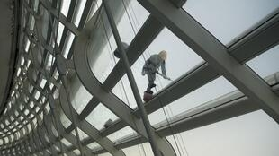 A worker cleans the roof of the National Speed Skating stadium at Beijing Olympic Park in March 2021 as preparations step up for the Winter Games