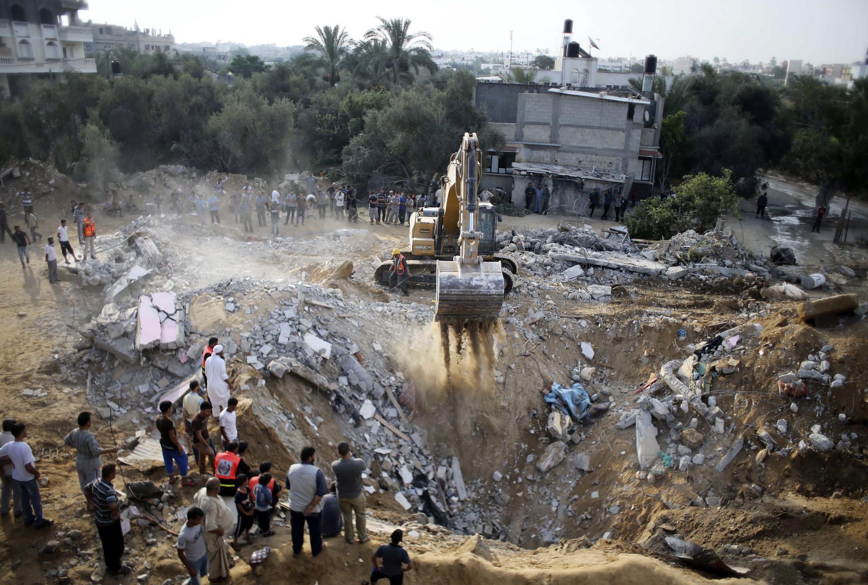 Palestinos retiram corpos de vítimas dos escombros, após intensos bombardeios de domingo (20).