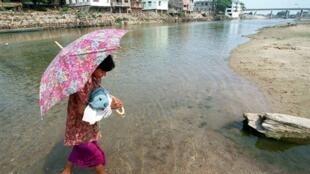 Une femme birmane, son enfant dans les bras, traverse le fleuve Moei afin de franchir la frontière séparant son pays de la Thaïlande.
