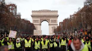 Des manifestants portant des gilets jaunes participent à une manifestation du mouvement des « gilets jaunes » sur les Champs-Élysées sous l'Arc de Triomphe à Paris, le 8 décembre 2018.