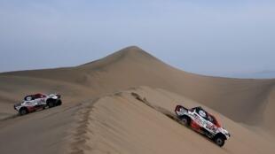 O piloto da Toyota Nasser Al-Attiyah do Qatar (R) e seu co-piloto Matthieu Baumel da França, seguido pelo piloto francês da Peugeot Sebastien Loeb e co-piloto Daniel Elena de Mônaco competem durante a etapa 9 do Dakar 2019 em torno de Pisco Peru. 16/01/19
