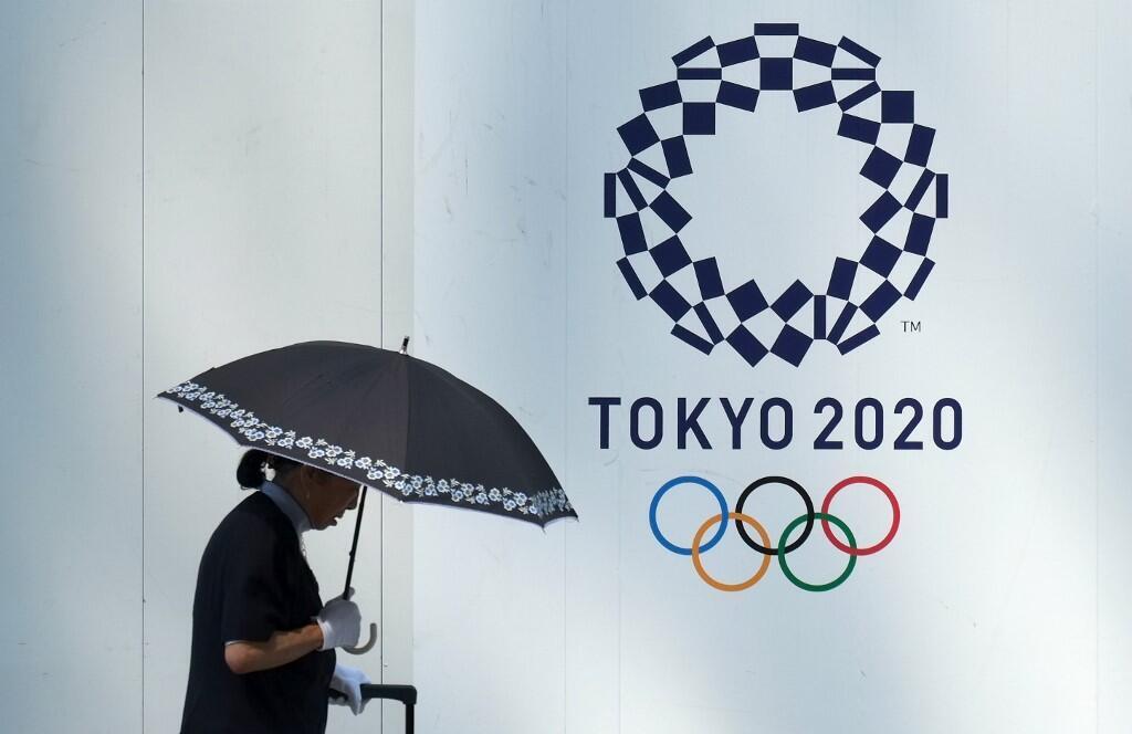 Un passante devant le logo des JO de Tokyo le 20 juillet 2017.