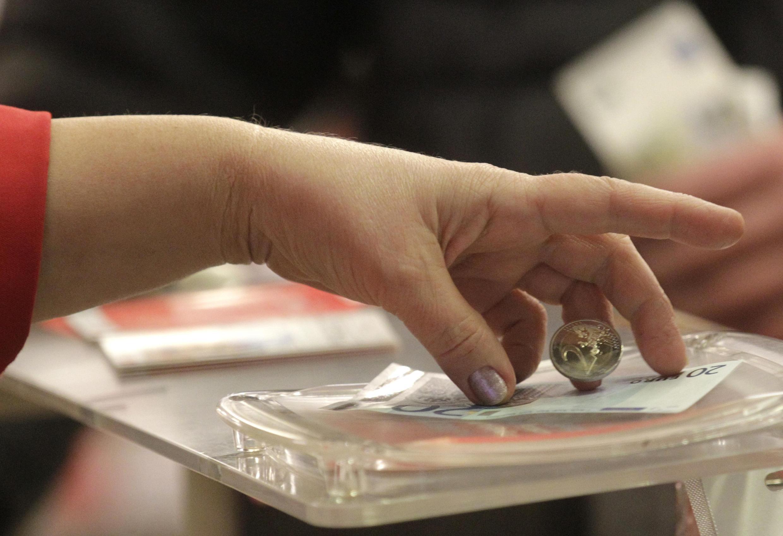 Кассир дает сдачу в евро в супермаркете в Риге 01/01/2014 (архив)