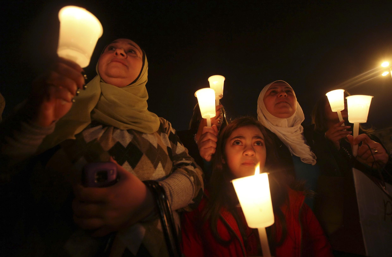 No dia 31, mulheres egípcias carregam velas em homenagem às vítimas das revoltas no Cairo.