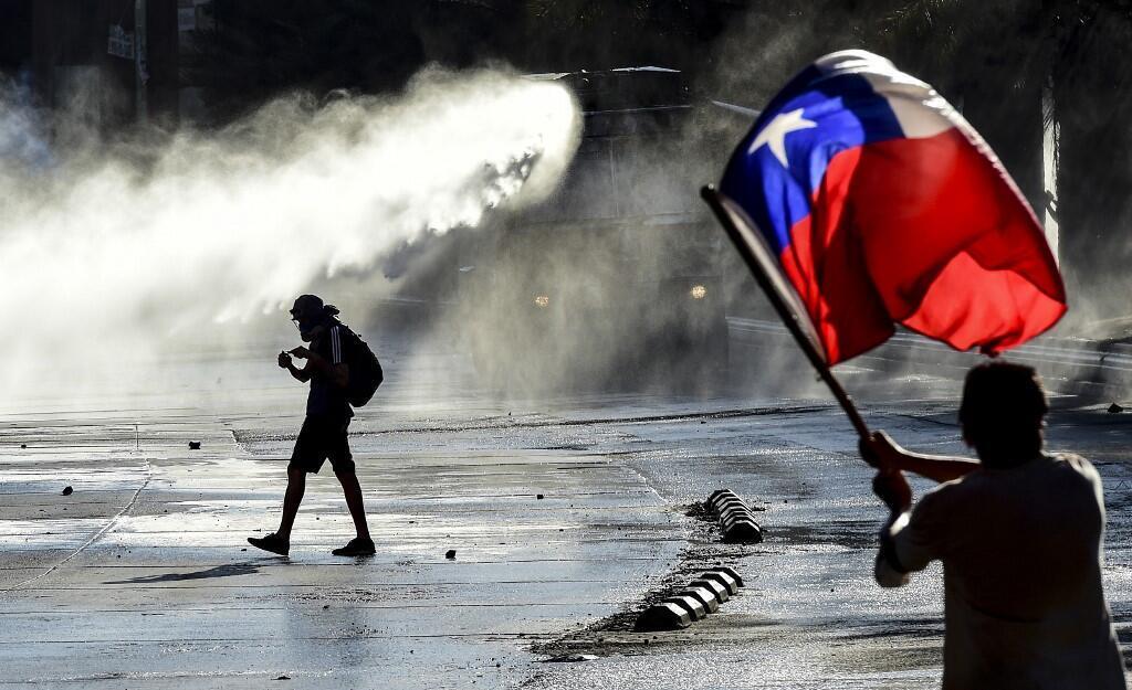 Manifestant brandissant un drapeau chilien alors que la police utilise des canons à eau, le 20 décembre 2019.