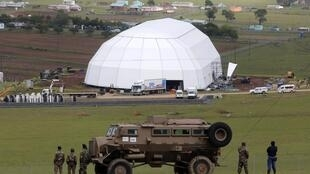 Soldiers and police in front of the tent in which the final ceremony before Nelson Mandela's burial will take place