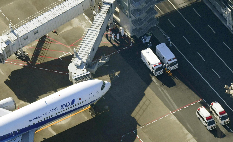 À l'aéroport de Tokyo-Haneda, des agents en tenue de protection s'affairent autour d'un avion en provenance de Wuhan, le 29 janvier 2020.