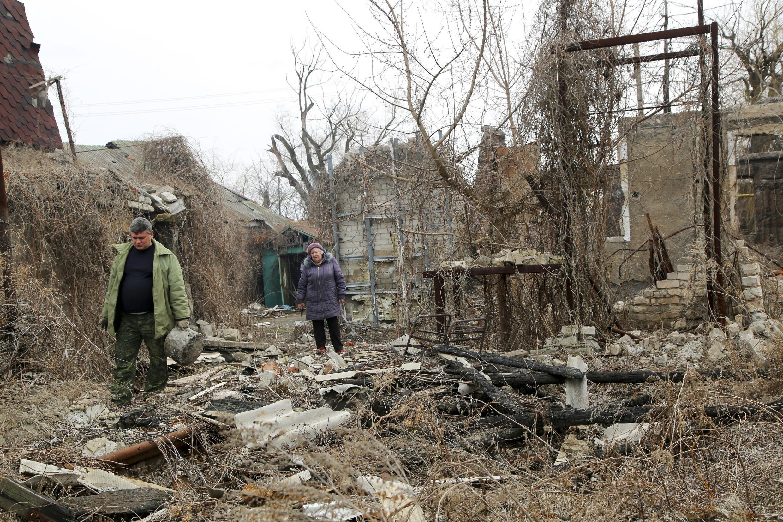 Wasu mazauna yankin 'yan aware dake gabashin kasar Ukraine, yayin duba yadda ruwan bama bamai ya ragargaza muhallinsu a yankin Donetsk.