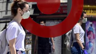 Una mujer con mascarilla y guantes se refleja en una cristalera mientras camina por una calle de Madrid el 21 de mayo de 2020