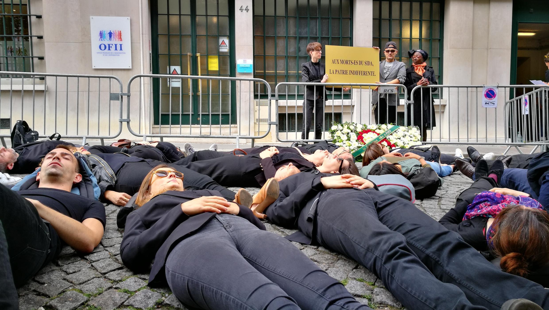 Une trentaine de militants de Aides, l'association de lutte contre le sida, se sont symboliquement allongés jeudi devant les locaux de l'Office français de l'immigration et de l'intégration, le 14 juin 2018.
