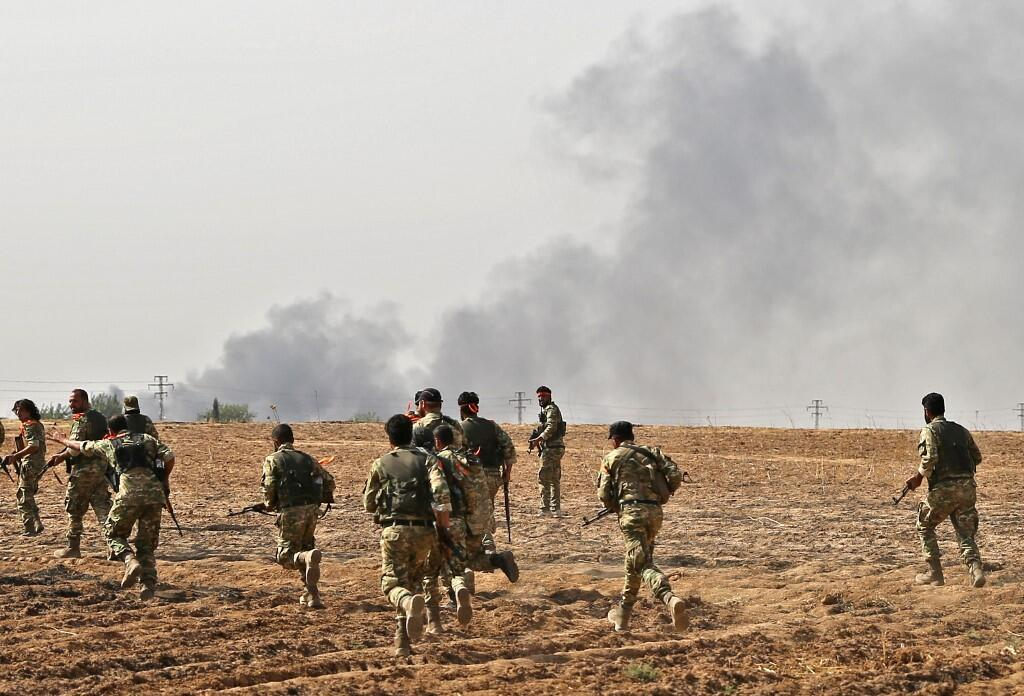 Pro-Turkish Syrian fighters cross the border into Syria as they take part in an offensive against Kurdish-controlled areas in northeastern Syria launched by the Turkish military, on October 11, 2019.