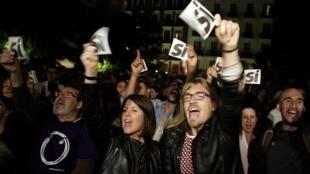 Partidários do Podemos festejam em Madri o resultado do partido nas eleições da Espanha, neste domingo (24).