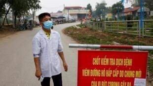 Nhân viên y tế tại một trạm kiểm soát đường vào làng Sơn Lôi, Vĩnh Phúc, Việt Nam bị cách ly. Ảnh chụp ngày 12/02/2020