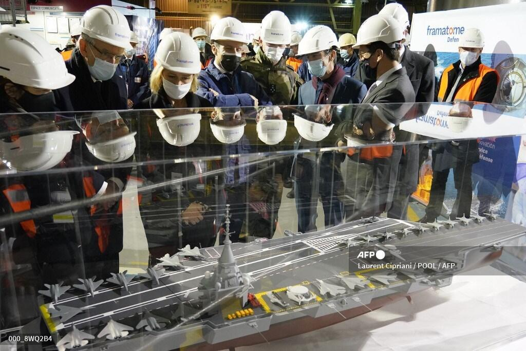 French President Emmanuel Macron (C) watches the model of a study of a new French Navy aricraft carrier which will be nuclear-powered, he announced, on December 8, 2020