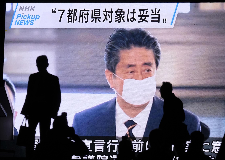 Una pantalla emite un informativo con la imagen de Shinzo Abe con mascarilla en el Parlamento de Japón, el 7 de abril de 2020 en Tokio