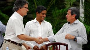 La Havane: le 1er août 2018, les négociateurs du gouvernement colombien Gustavo Bell (G) et Pablo Beltran (D) se serrent la main sous le regard du médiateur cubain, Ivan Mora.