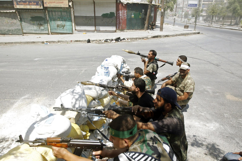 Rebeldes do Exército Livre Sírio durante combates contra as forças de Bashar Al-Assad na tarde de domingo em Aleppo, a segunda maior cidade do país.