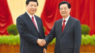 图为习近平与胡锦涛握手照片