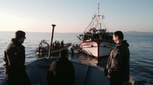 En Grèce, des gardes-côtes remorquent un bateau où des migrants essayaient de rejoindre l'Europe, le 18 mars 2014.