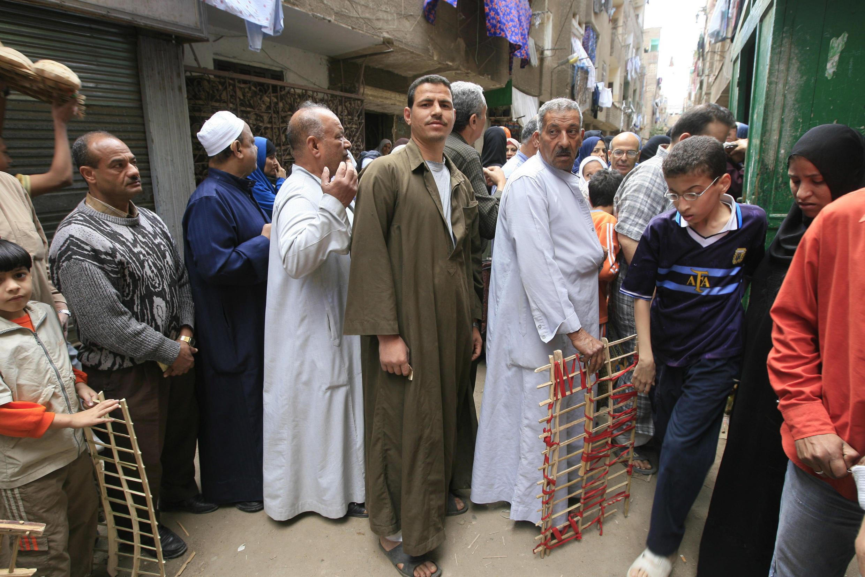 Des Egyptiens font la queue devant une boulangerie dans un quartier populaire du Caire.