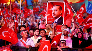 Supporters of Turkish President Recep Tayyip Erdogan wave national flags as they listen to him through a giant screen in Istanbu