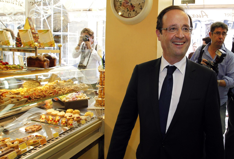 Le nouveau président français, François Hollande entre dans une boulangerie pendant sa visite à Tulle, le 11 mai 2012.