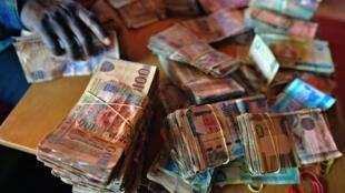 Un homme compte des liasses de dalasis, la monnaie gambienne, à Banjul.