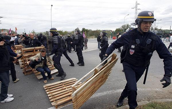 Police clear barricades from an oil depot
