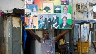 Un supporter de Cellou Dalein Diallo brandissant une affiche pour sa campagne présidentielle à Conakry, le 06 novembre 2010.