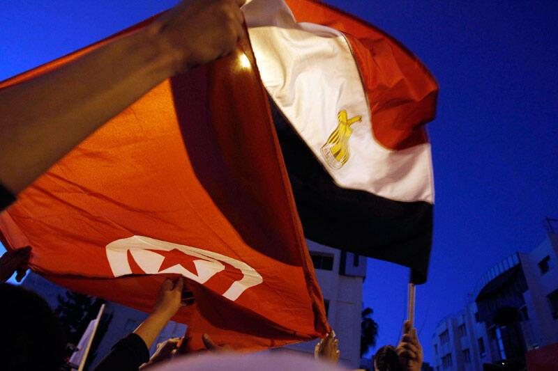 Tunisiens et Egyptiens vivant à Tunis brandissent les drapeaux des deux pays pour célébrer  la démission de l'ex-président egyptien Hosni Moubarak, devant l'ambassade d'Egypte à Tunis, le 11 février 2011.