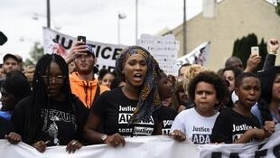 Assa Traoré (centre) marches for justice for her brother Adama.