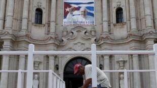 Un hombre instala una alfombra en uno de los podios de la catedral de La Habana, el 17 de septiembre de 2015 en Cuba.