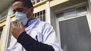 Um enfermeiro argelino veste sua máscara de proteção em frente à Unidade Especial do Hospital El-Kettar, onde um caso de coronavírus foi anunciado, na capital Alger. 26 de fevereiro de 2020