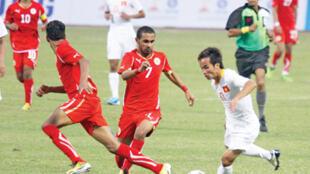 Đức Thiện của O. Việt Nam (trắng) trong trận thắng tưng bừng Bahrain (đỏ) 10/11/2010