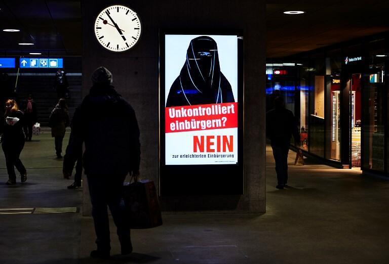 Gare de Zürich, le 7 février 2017. Des affiches de campagne contre possibilité aux immigrés de 3e génération de devenir plus facilement Suisse montrent une femme en burqa.