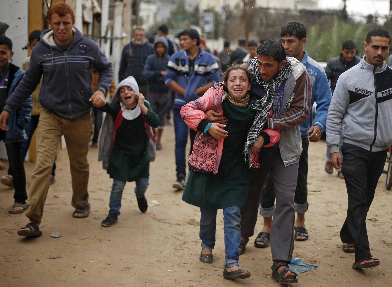 Filhas do palestino Fadel Mohammed Halaoua, no centro da imagem, choram após a morte do pai, abatido por soldados israelenses.