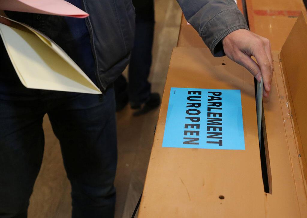 یک شهروند بلژیکی در یکی از دفتر رایگیری در «لیمال» واقع در منطقۀ «والونی» بلژیک رای خود را برای انتخابات پارلمانی اروپا به صندوق می اندازد - ٢۶ مه ٢٠١٩