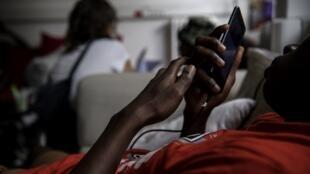 Un jeune homme utilise un téléphone portable en attendant un rendez-vous dans un centre MSF (Médecins Sans Frontières / Médecins Sans Frontières) pour mineurs sans famille à Pantin près de Paris le 3 juillet 2018.
