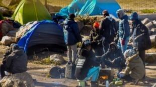 Des migrants s'apprêtent à manger dans un camp, près de Calais, en mars 2018.