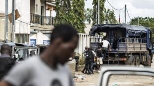 Des partisans de Jean Ping sont embarqués dans des camions de la police, au quartier général de du candidat de l'opposition, le 1er septembre à Libreville.