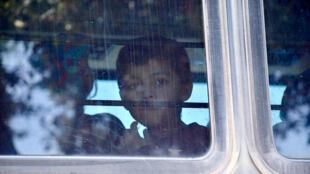 Un enfant regardant par la fenêtre d'un bus. (Image d'illustration)