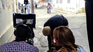 Oumar Diack (à gauche, de dos), co-réalisateur de la série Wara, tourne une scène dans les rue de Saint-Louis.